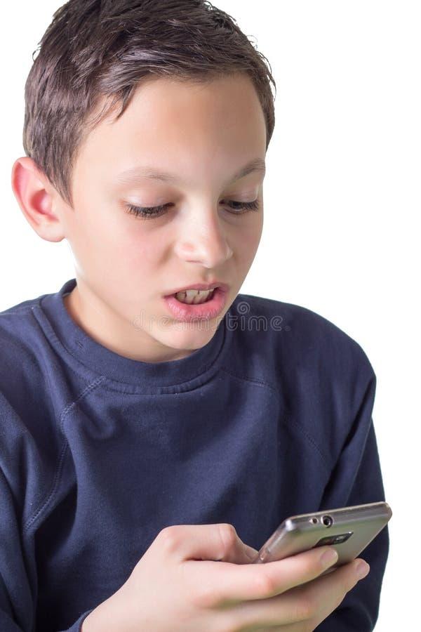 使用smartphone的年轻男孩。 免版税图库摄影