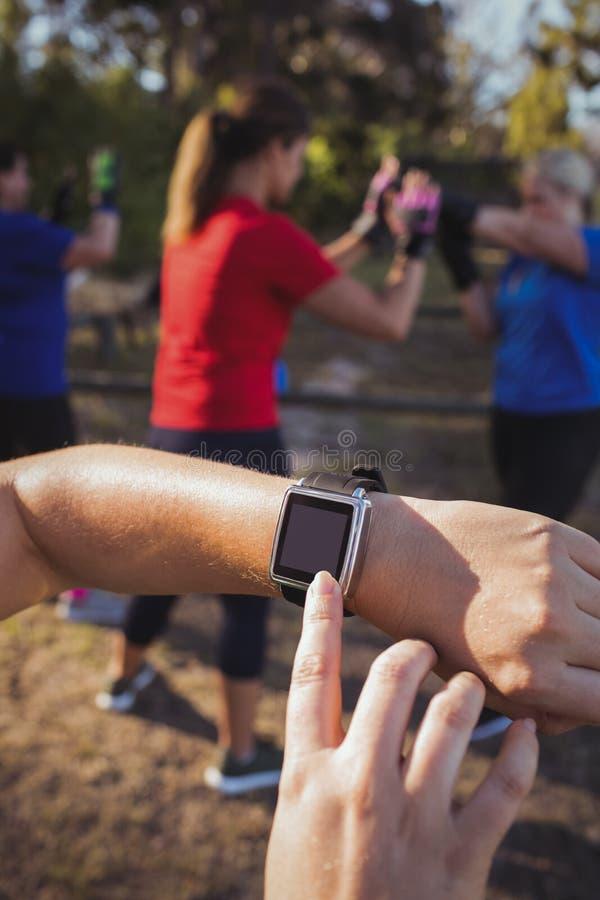 使用smartwatch的妇女的手在新兵训练所 免版税库存照片
