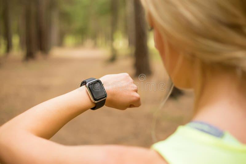 使用smartwatch的活跃妇女 库存图片