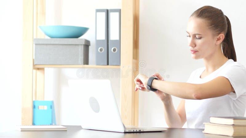 使用Smartwatch,浏览电子邮件的妇女在工作在办公室 免版税库存图片