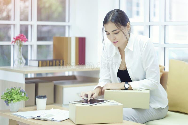 使用tabtet计算机的企业主证实和检查装箱单顺序、组装箱子、运输的小包包裹和交付 免版税库存照片