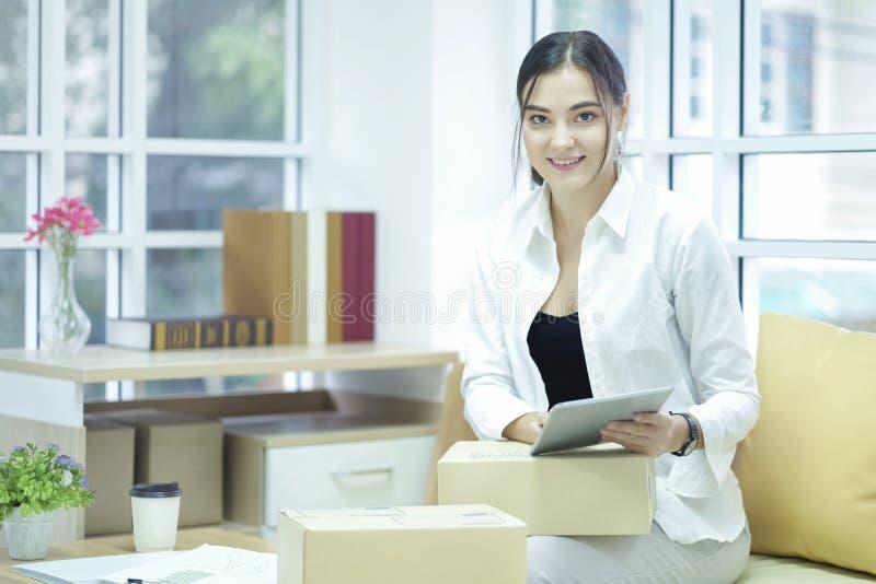 使用tabtet计算机的企业主证实和检查装箱单顺序、组装箱子、运输的小包包裹和交付 库存照片