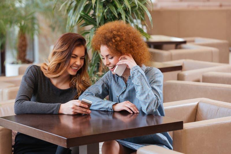 使用thir智能手机的两名愉快的妇女在咖啡馆和笑 免版税库存照片