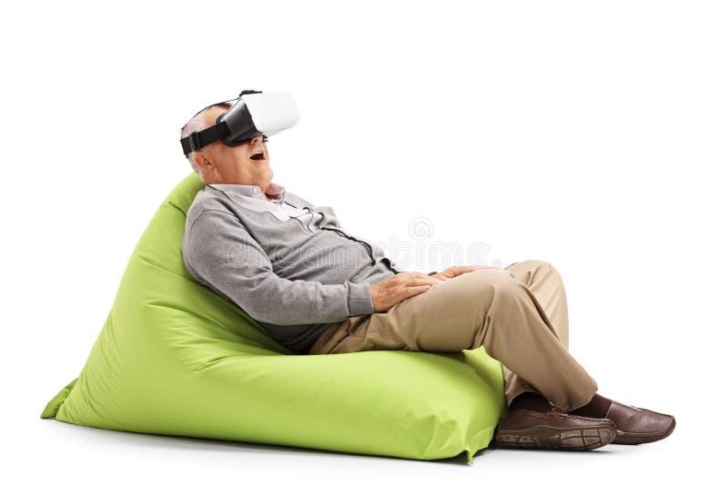 使用VR耳机的前辈供以座位在装豆子小布袋 免版税库存图片