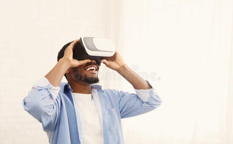使用VR耳机的快乐的黑人在家 免版税库存图片