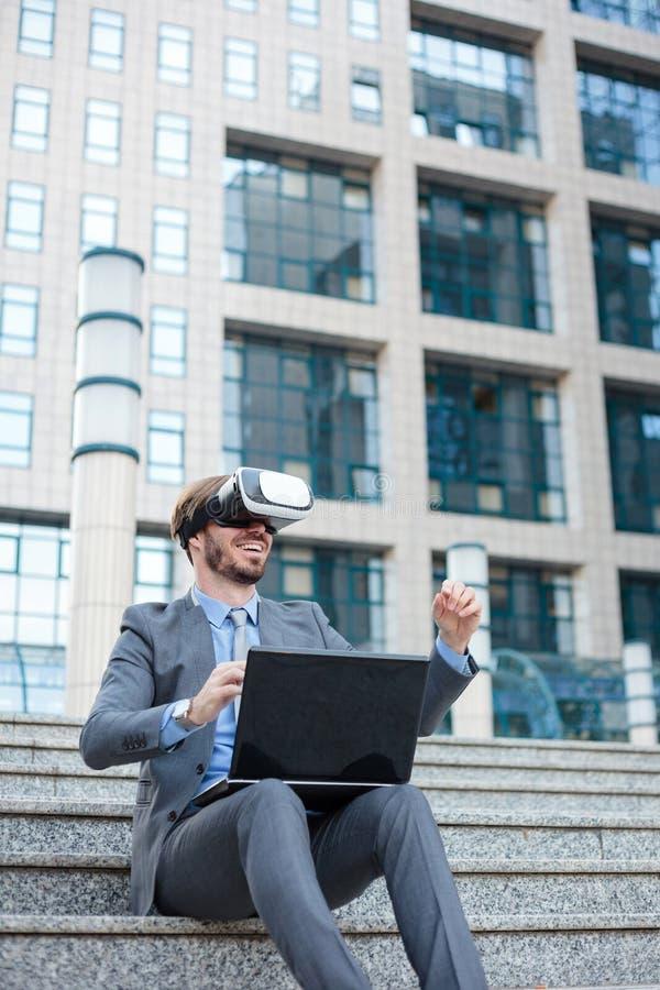 使用VR风镜的年轻商人和做手势,运作在办公楼前面的一台膝上型计算机 库存照片