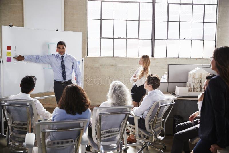 使用whiteboard的Businessmastands在介绍时 免版税库存照片
