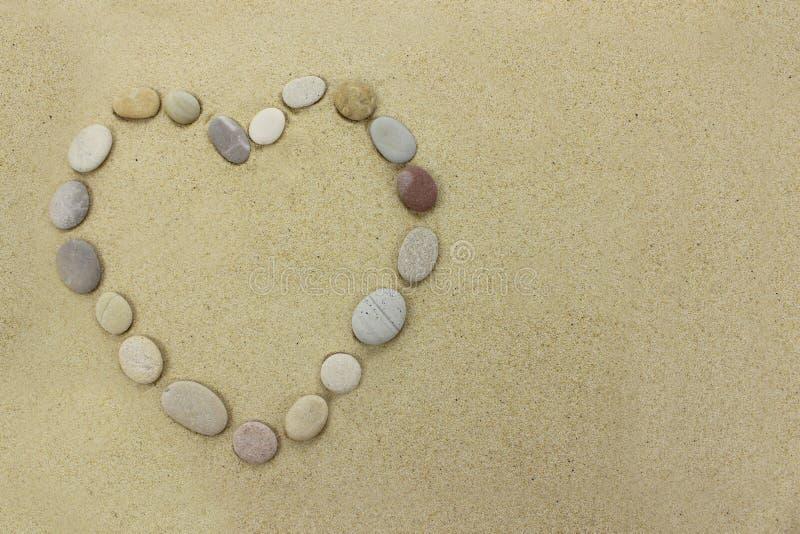使石头靠岸以在一个沙滩的心脏的形式 库存照片