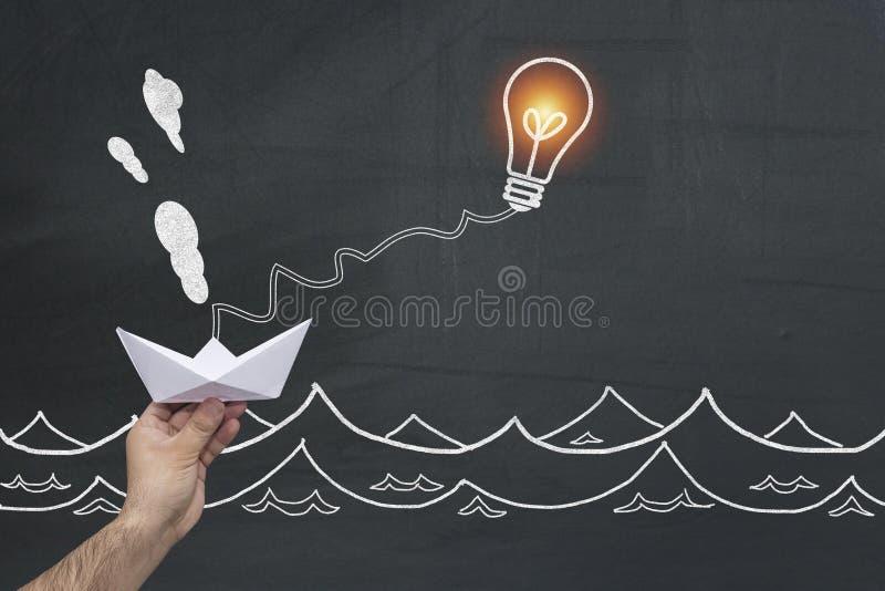 使移动纸小船的电灯泡作为聪明想法的解决的成功隐喻经济和运输挑战 免版税库存图片