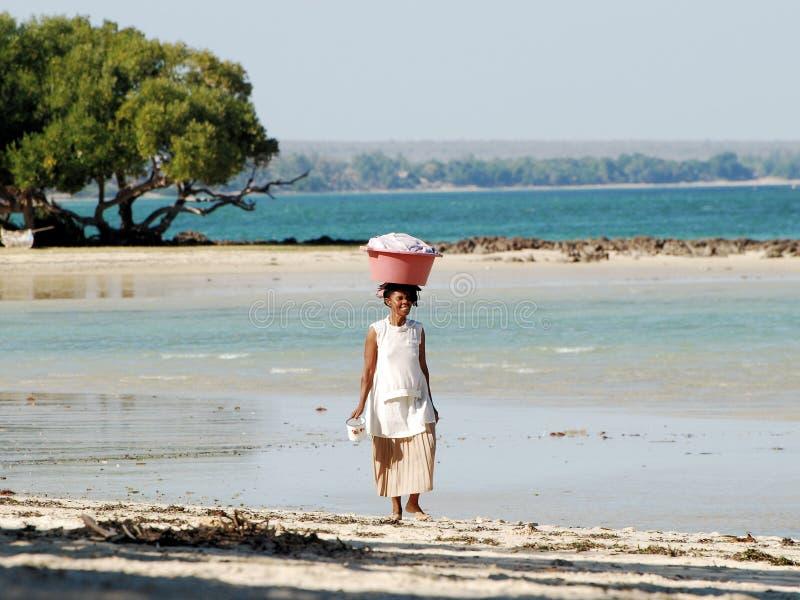 使缩回水和走的妇女靠岸有篮子的在她的头,马达加斯加 图库摄影