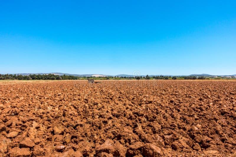 使耕地环境美化,反对蓝天的被犁的红色土壤看法  库存图片