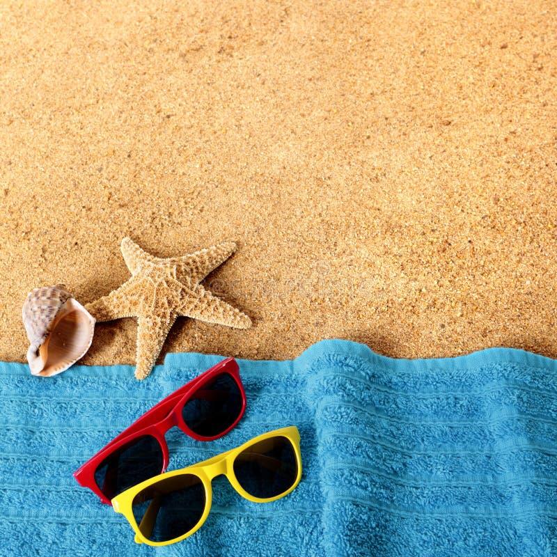 使背景边界太阳镜、毛巾、海星和海靠岸 图库摄影