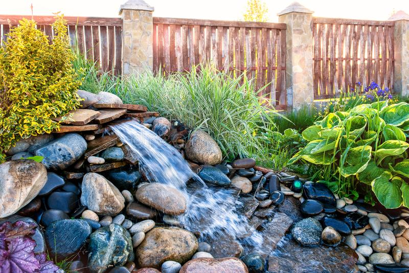 使设计、高山幻灯片与一个大喷泉和一条小河环境美化 库存图片