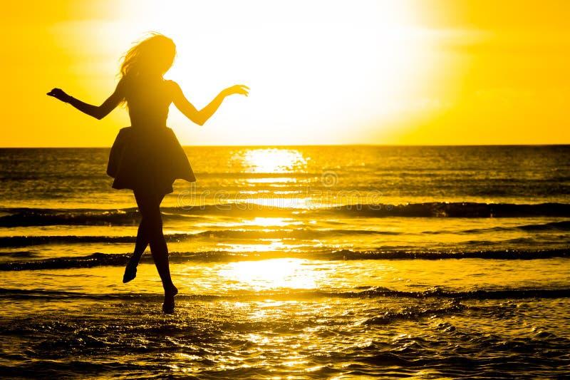 使跳舞健康生存日落假期生命力妇女的无忧无虑的概念靠岸 假期vita 库存图片