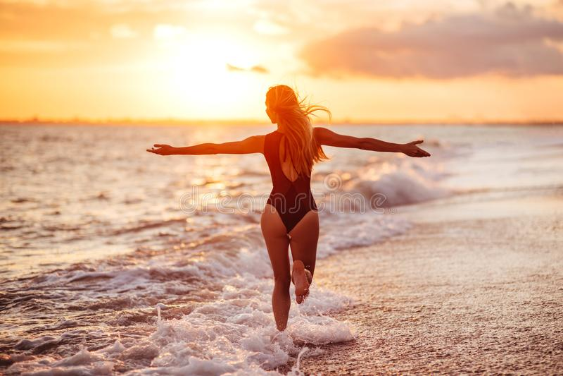 使跳舞健康生存日落假期生命力妇女的无忧无虑的概念靠岸 免版税库存照片