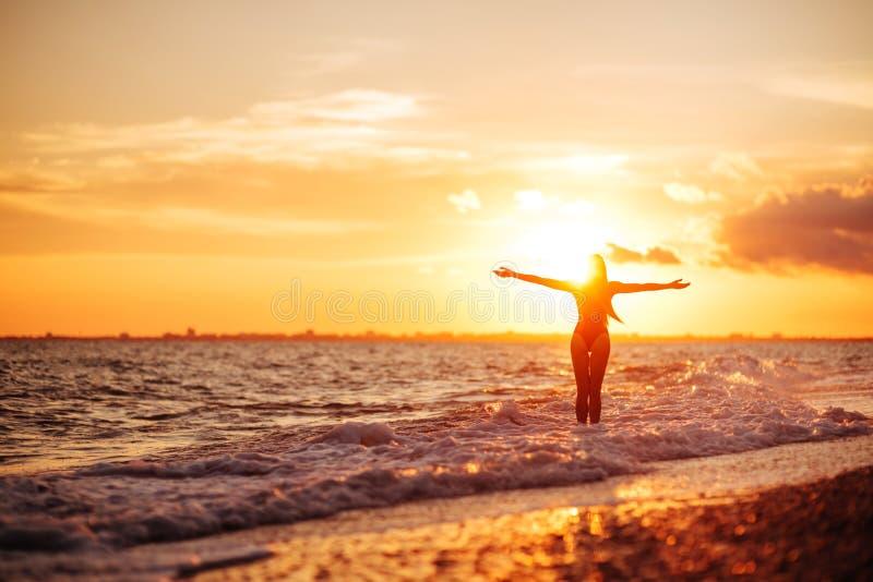 使跳舞健康生存日落假期生命力妇女的无忧无虑的概念靠岸 免版税图库摄影