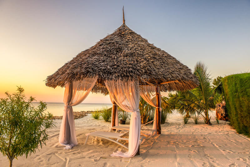 使躺椅在日落,桑给巴尔,坦桑尼亚靠岸 库存图片