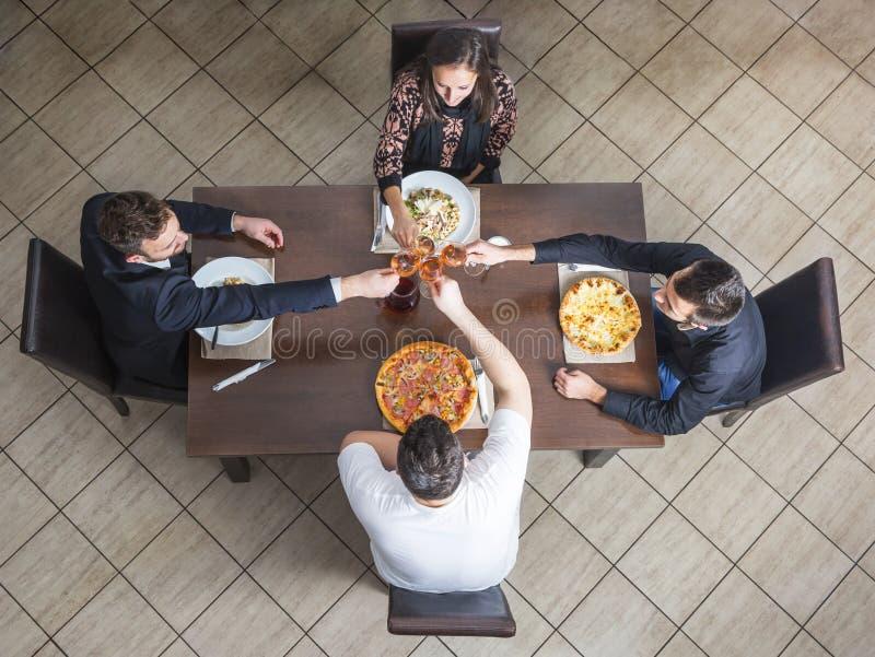 使酒杯叮当响的朋友在餐馆 图库摄影