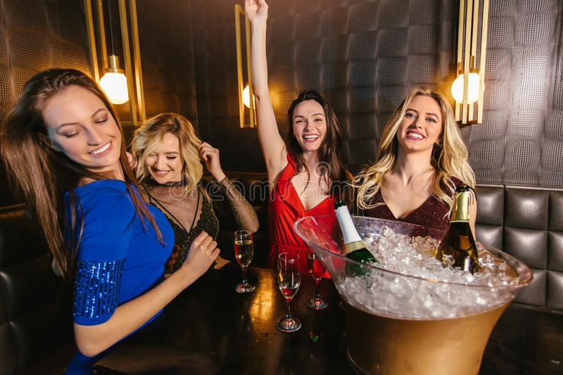 使香槟玻璃叮当响和庆祝在夜总会的妇女 免版税图库摄影