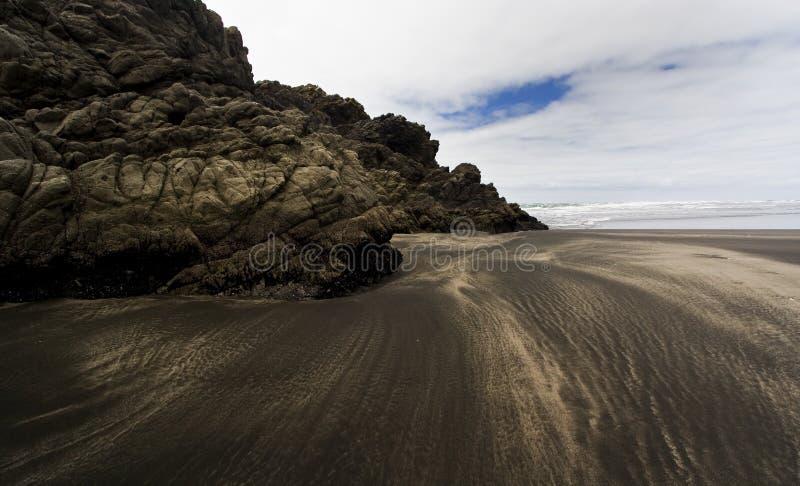 使黑色karekare礁石沙子靠岸 库存图片