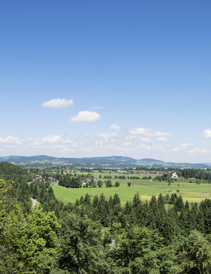 使从Hohenschwangau城堡的看法环境美化在垂直的样式 夏天蓝天和美好的自然 免版税库存照片