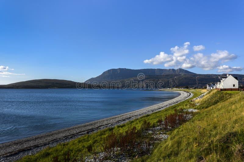 例外美丽的海岸在有房子白色行的北苏格兰高地在透明的蓝色海, Assynt, Sc的 库存图片