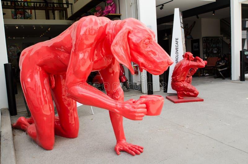 侍从和果渣画廊导致犀牛和狗,图象展示红色狗雕塑当代艺术雕塑  免版税图库摄影