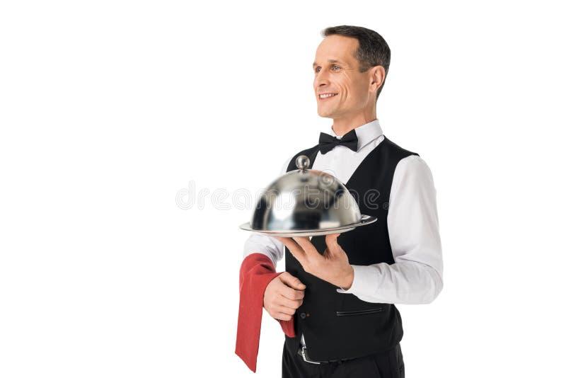 侍者一致的拿着的盘子的微笑的人有盖子的 免版税库存图片