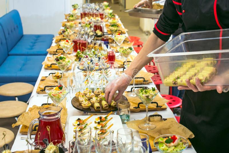侍者与可口和开胃菜的服务桌 承办酒席服务 免版税库存照片