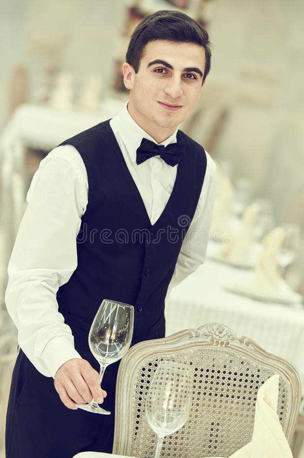 侍者人服务在餐馆的宴会桌 免版税库存照片