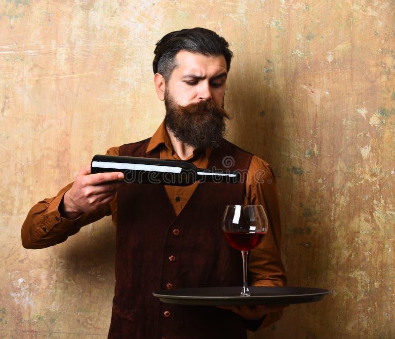 侍者倒红葡萄酒入从瓶的玻璃在盘子 免版税库存照片