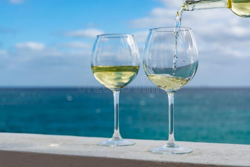 侍者倾吐的杯在室外大阳台的白葡萄酒与海v 库存图片