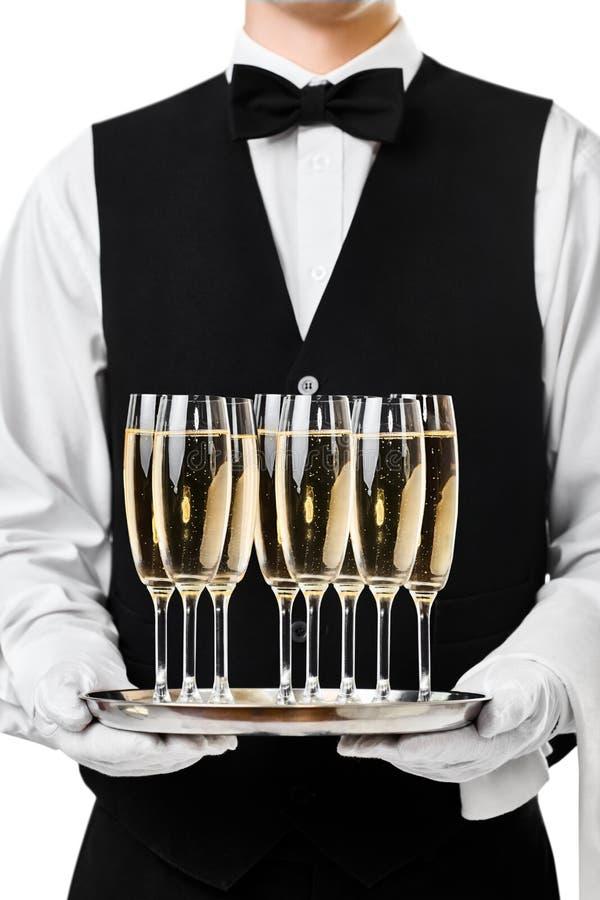 侍者在盘子的服务香槟 免版税库存照片