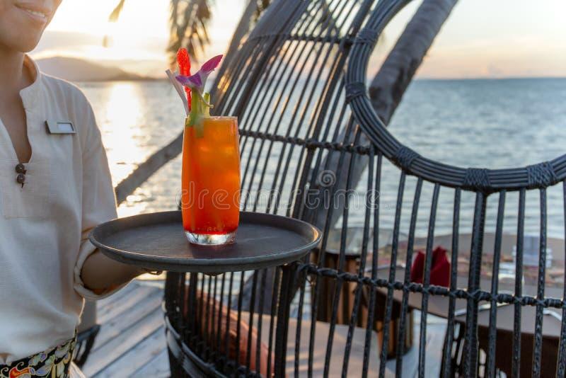 侍者服务的杯由海滩的鸡尾酒在日落 库存照片