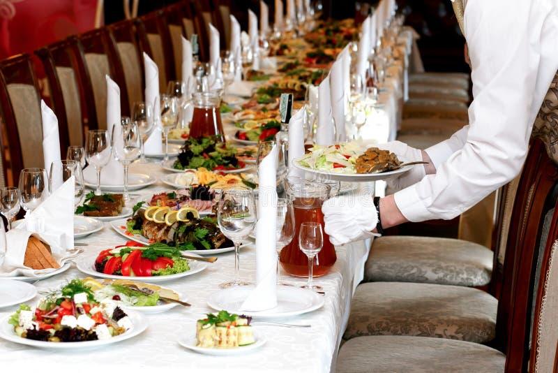 侍者服务食物在豪华桌上设置了在结婚宴会,加州 库存照片