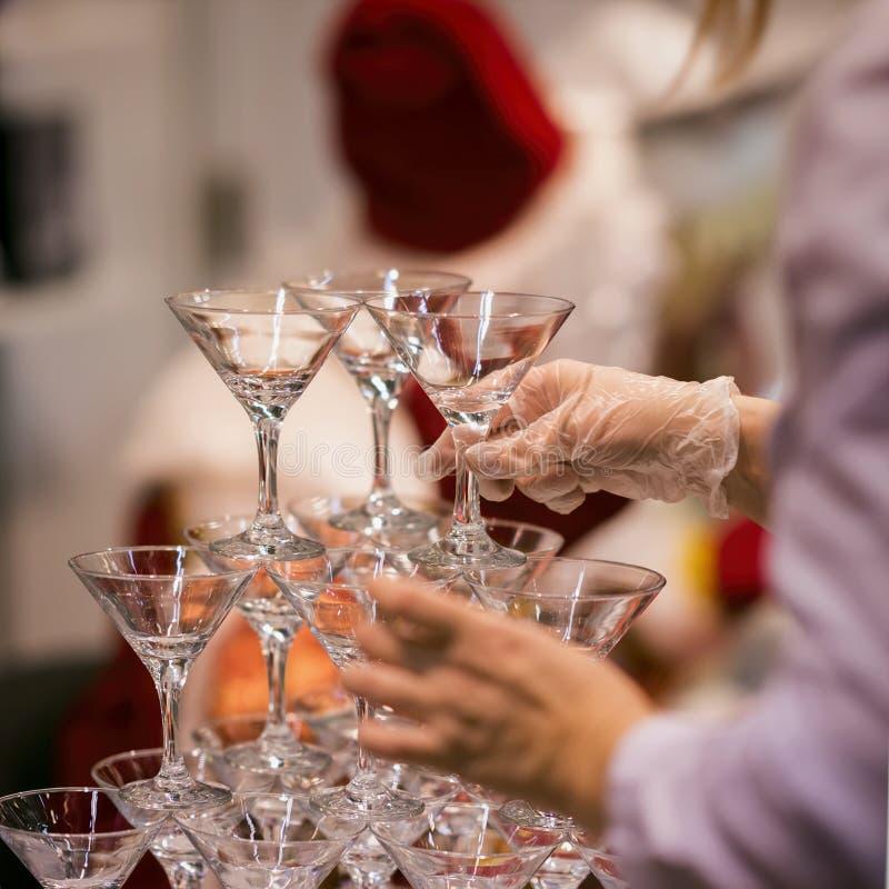 侍者的手做金字塔从饮料的玻璃,酒,香槟,欢乐心情,庆祝的橡胶手套的 免版税库存图片
