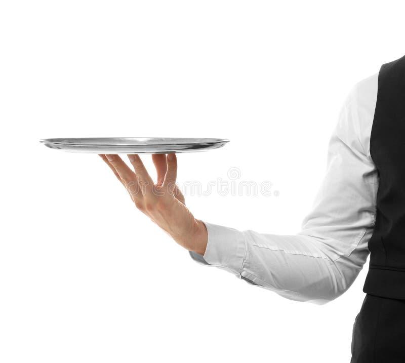 侍者的手有金属盘子的在背景 免版税库存照片