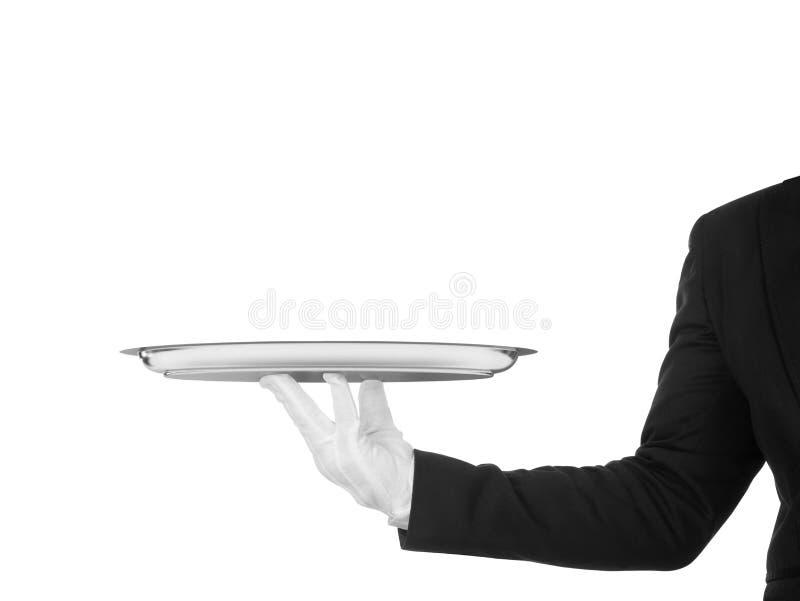 侍者的手白色手套的与银色盘 免版税库存照片