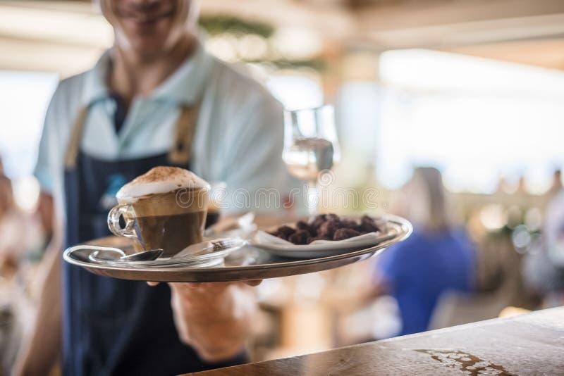 侍者运载从工作台面的咖啡给resta的客户 免版税库存图片