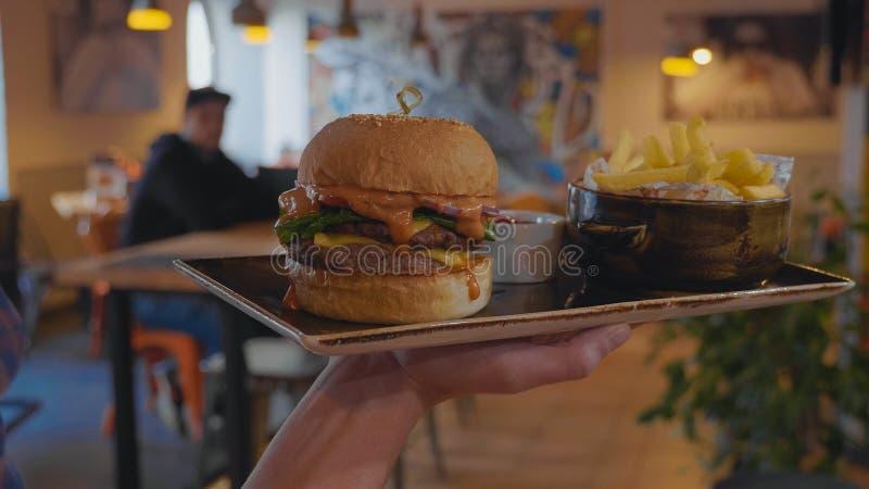 侍者运载汉堡和炸薯条给客户在快餐咖啡馆 免版税库存照片