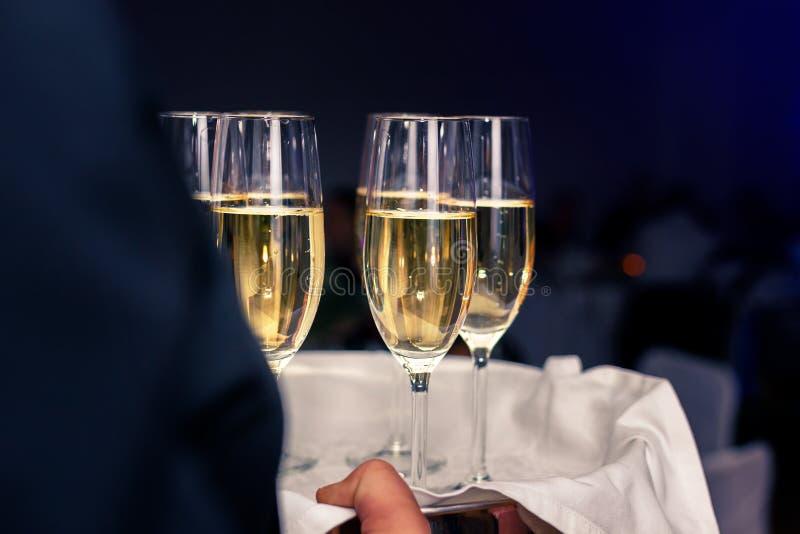 侍者运载的香槟玻璃充满在盘子的香槟 免版税图库摄影