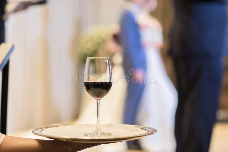 侍者carring有红葡萄酒玻璃的板材 玻璃 蓝色dof玻璃浅酒 免版税图库摄影