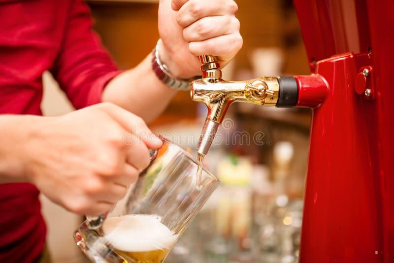 侍酒者倾吐的啤酒草稿在客栈,酒吧 免版税图库摄影