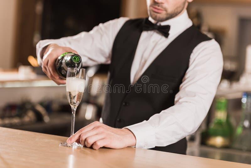 侍酒者倾吐的香槟到玻璃里 免版税图库摄影