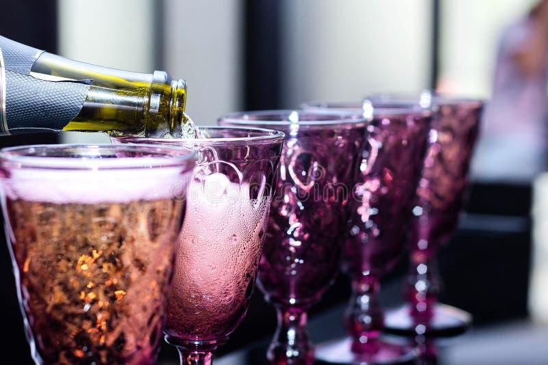 侍酒者倾吐的香槟到玻璃里 免版税库存照片
