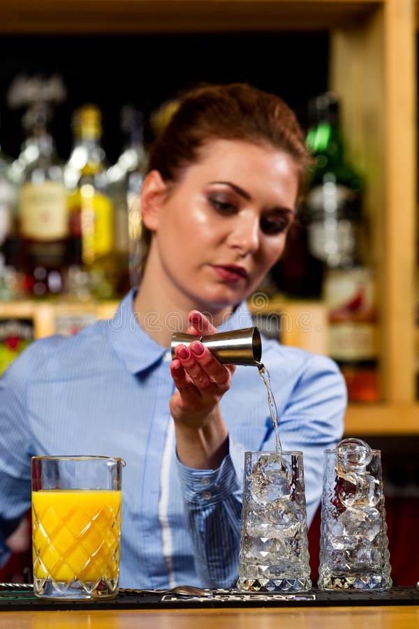 侍酒者准备鸡尾酒在酒吧 免版税库存图片