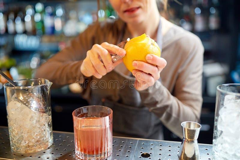 侍酒者剥鸡尾酒的橙皮在酒吧 库存图片