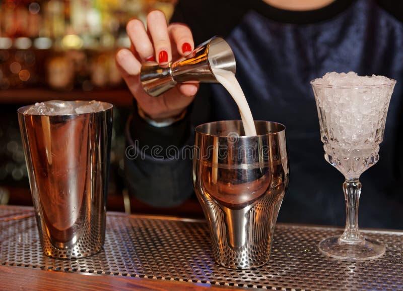 侍酒者加牛奶到振动器 免版税库存图片