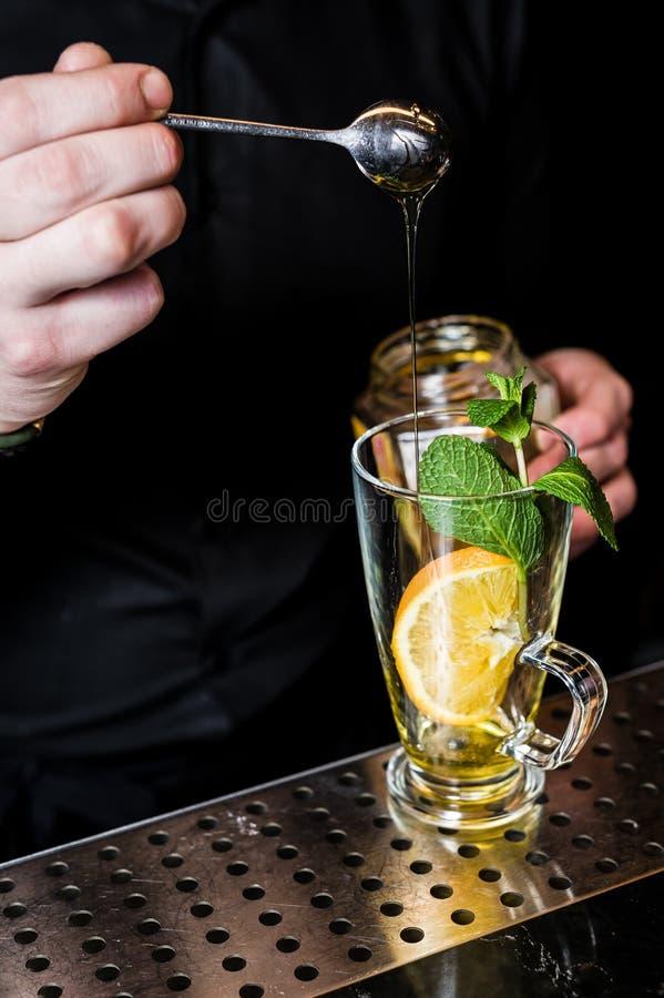 侍酒者在玻璃,黑暗的背景中准备果子茶用蔓越桔 免版税库存照片
