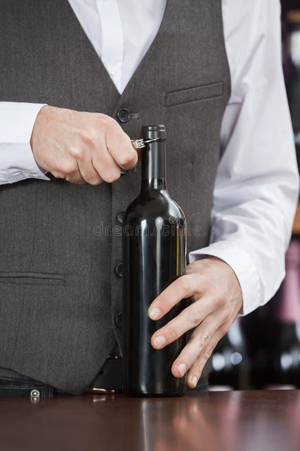 侍酒者开头酒瓶的中央部位 免版税库存图片